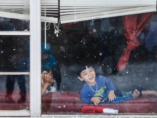 As snow falls outside Jabeeak Magar, 3, (cq) watches