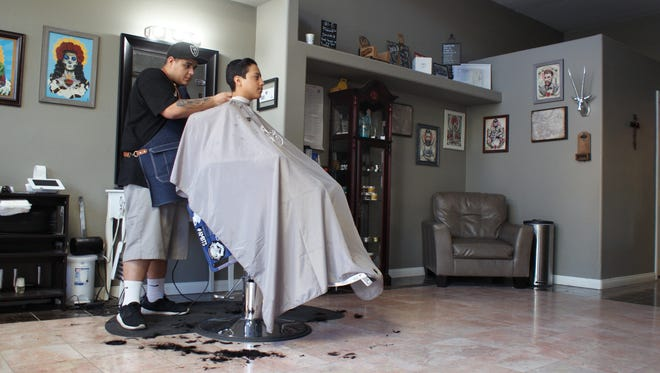 A barber cuts a client's hair at the Old Town Barber Shop on Miles Avenue.