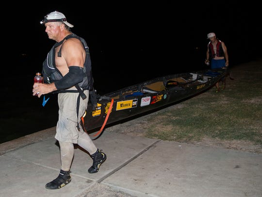 Wayne Thorp and Wes Wyatt carry their canoe to the