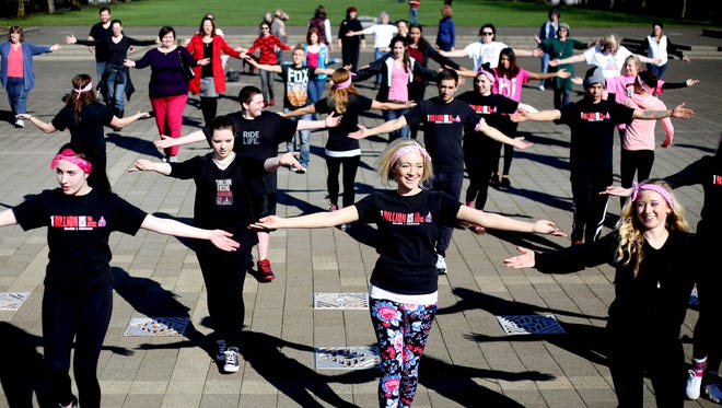 People dance at a One Billion Rising rally to raise awareness to end violence against women and girls worldwide at the Oregon State Capitol in Salem on Saturday, Feb. 14, 2015.