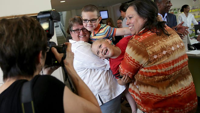 Dana, left, and Diane Shaw, of Rochester Hills, hold their adopted sons Jacob, 5, and Charlie, 6, during a press conference at Affirmations in Ferndale on Friday, June 26, 2015.