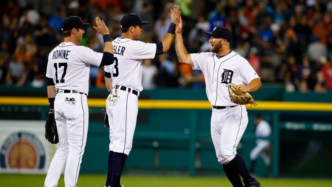 Jul 15, 2016; Detroit, MI, USA; Detroit Tigers third baseman Andrew Romine second baseman Ian Kinsler and left fielder Tyler Collins celebrates against the Kansas City Royals at Comerica Park.