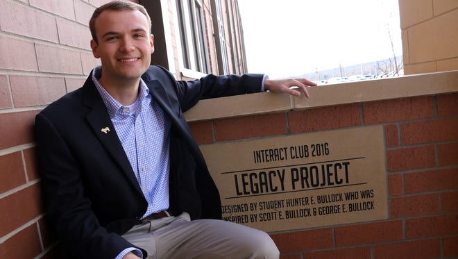 Stewarts Creek grad Hunter Bullock poses in front of the plaque that marks his family's leadership with the Legacy Project, a brick-paver courtyard created at the entrance to the school.