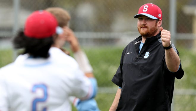 South Salem head coach Max Price fist-bumps players after an inning of the McKay vs. South Salem baseball game at Gilmore Field in Salem on Tuesday, April 11, 2017.