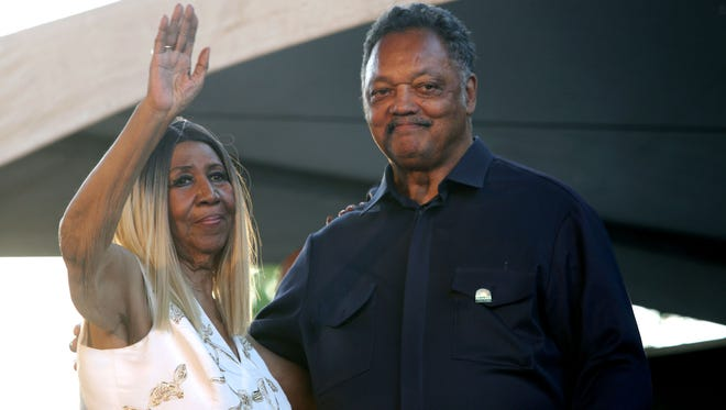 Aretha Franklin and the Rev. Jesse Jackson wave to the crowd from the Madison Central stage.