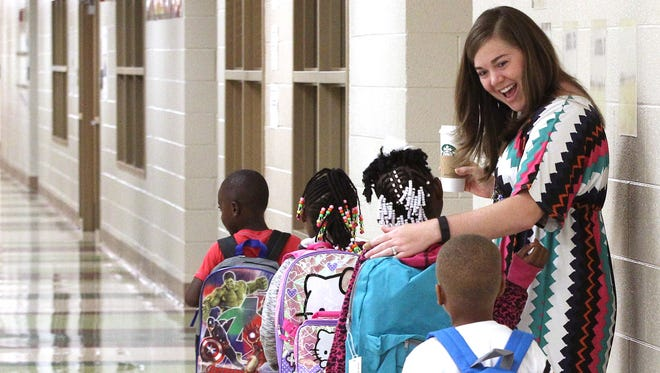 Ashley James, a first grade teacher at Nevitt Forest Elementary School, greets children at the beginning of the school day in Anderson last year.