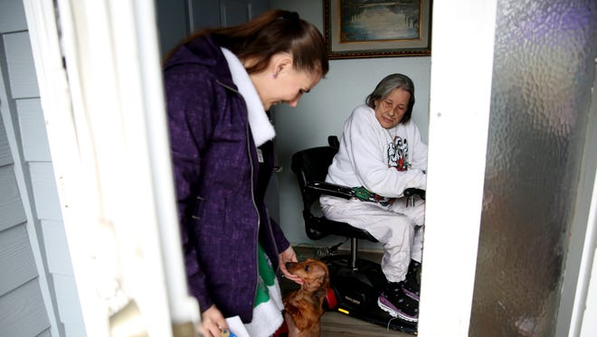 Sheree Kelly, a program assistant with Meals on Wheels, is greeted by Snoopy, the 8-year-old miniature dachshund of Suzy Jenks, 75, as she delivers to clients in Salem on Thursday, Dec. 21, 2017. The program is expecting to begin using reusable trays in the next month for food delivery.