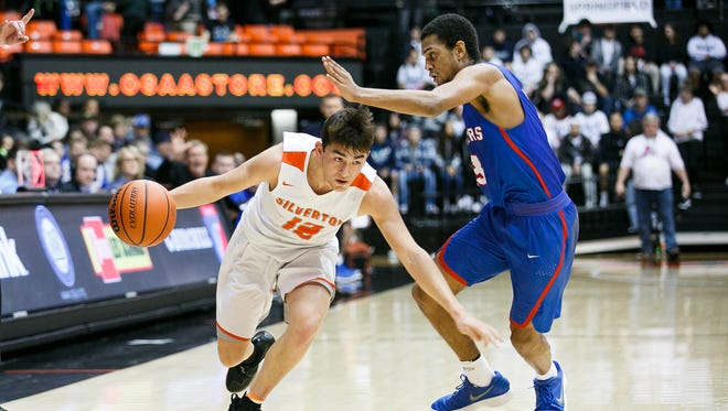 Silverton's David Gonzales (12) ducks under the arm of Churchill's Isaiah Wallace (3) in a 5A state quarterfinal game on Wednesday, March 7, 2018, at Gill Coliseum in Corvallis. The No. 1 seed Silverton Foxes lost 53-51.