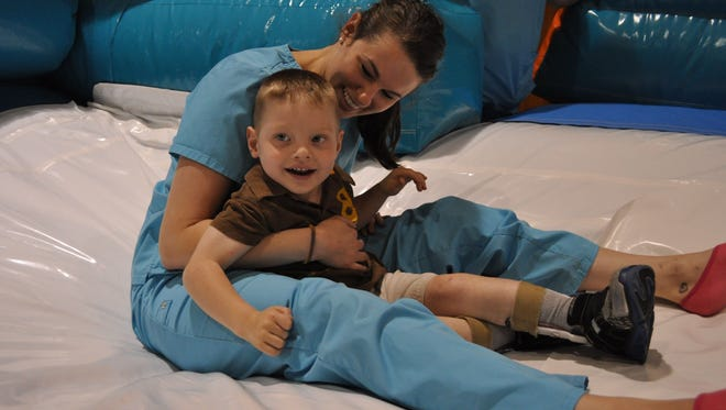 Coen Davis enjoys an inflatable slide with Sydney Bordelon Thursday evening during Buddy night at First United Methodist Church in Alexandria.