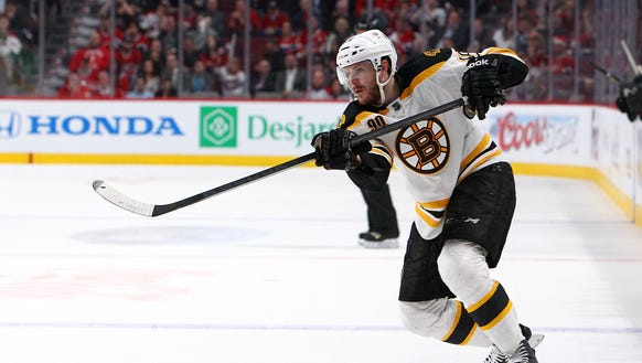 Kevan Miller of the Boston Bruins shoots the puck against