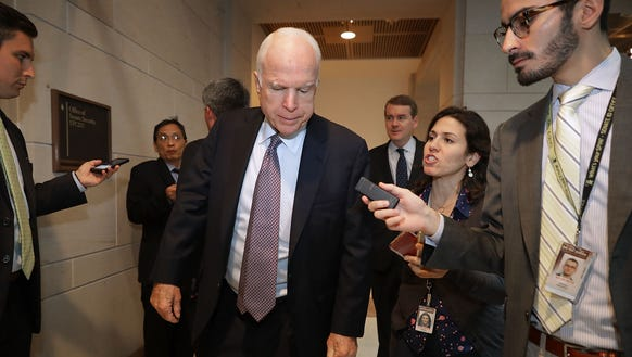 Sen. John McCain talks to reporters as he arrives for