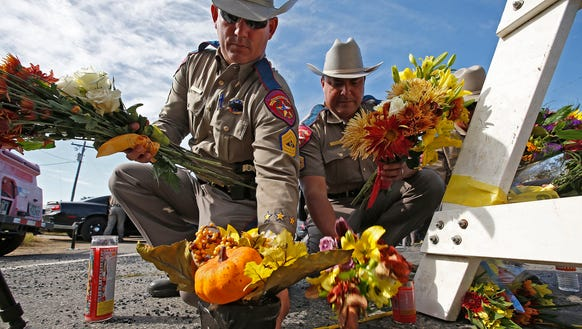 Texas State Troopers pick up flowers left for a memorial