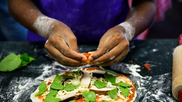 Jaryn Gerald, 9, makes a veggie pizza during a Healthy