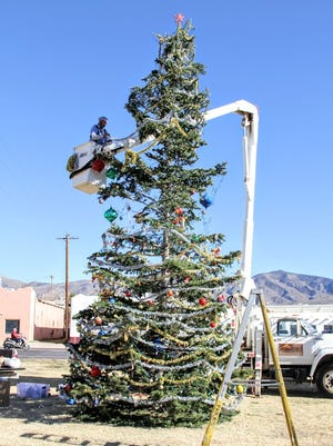 A City employee hangs lights and ornaments on the Christmas Tree donated by the Lincoln National Forest at the Airborne Memorial at 10th Street and White Sands Boulevard Thursday.