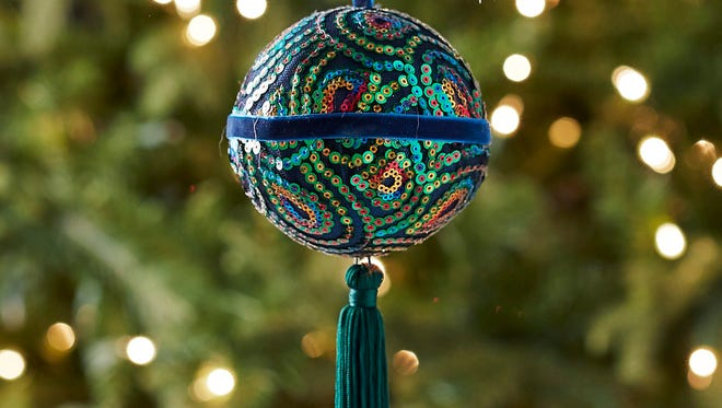 This photo provided by Pier 1 Imports shows a peacock sequin ornamental ball that brings in the holiday colors with a touch of global exoticism. Blue, green and turquoise continues to find favor with many home decorators for the holidays. For those who love to decorate, there's no time like the holidays for adding some fun, festive touches to our living spaces. (AP Photo/Pier 1 Imports)