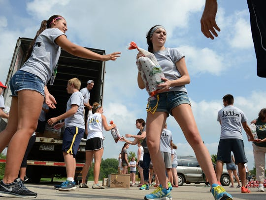 "St. Norbert College students unload potatoes from a semi trailer, for distribution to area food pantries, as part of the eleventh annual ""Into the Streets"" community service day event."