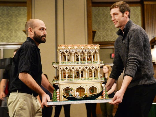 Brian Baker, left, and Jason Clodfelter carry a gingerbread house by Glenda Tant top to the winners table during the 25th annual Gingerbread House Competition at the Grove Park Inn November 20, 2017 in Asheville. The entry won second place.