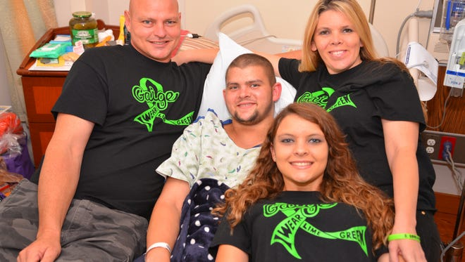 "Gaige Robbins of Melbourne is diagnosed with  nonHodgkins Lymphoma and has been undergoing chemo and radiation treatments.  His family is selling shirts that say ""Gaige. I wear lime green"" in honor of their 19-year-old son. Gaige surrounded by his family-  his dad Shane, mom Christa and sister Kaylie."