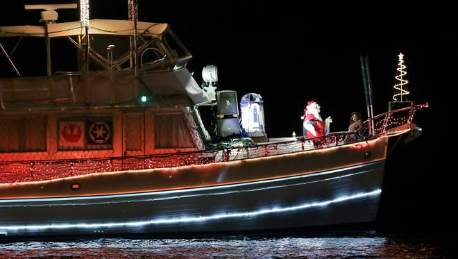 Santa waves to spectators while looking over the bow of a boat on Dec. 2, 2016, during the Indian River County Christmas Boat Parade in Vero Beach.