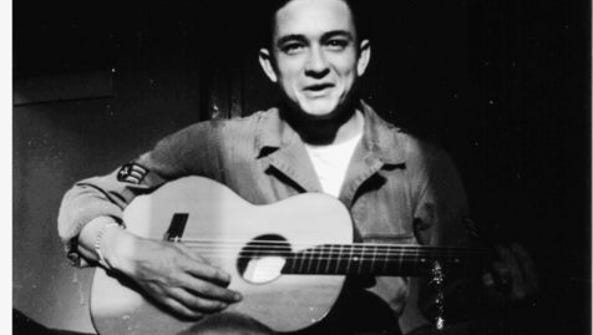 Johnny Cash holds his $10 guitar. He sold appliances
