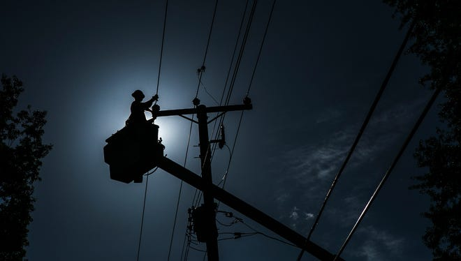 "May 31, 2017 - MLGW employees Matthew ""The Dip"" Depadova and Robert Fatimer (not pictured) work on power lines on Point Church Ave. in Frayser on Wednesday afternoon. A storm swept through Memphis late on Saturday night causing thousands of MLGW customers to be without power."