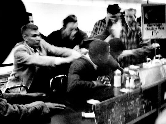 Several white men, left, attempt to drag some of the black students from the lunch counter where they staged a sit-down against segregation in the downtown Woolworth's store Feb. 27, 1960. Police marched into three variety stores and arrested 73 students, most of them blacks seeking lunch counter integration.