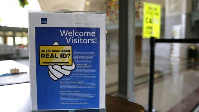 In this 2016 file photo, a sign informs visitors of the federal government's Real ID act, at a courthouse in Washington state. For the more than half-a-million people with a Massachusetts driver's license or identification card expiring this summer, the Registry of Motor Vehicles is offering to waive the fees for upgrading to a REAL ID next year if people renew their standard licenses online by Aug. 12.