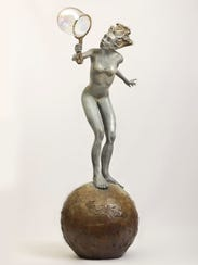 A girl blows bubbles in this whimsical sculpture.