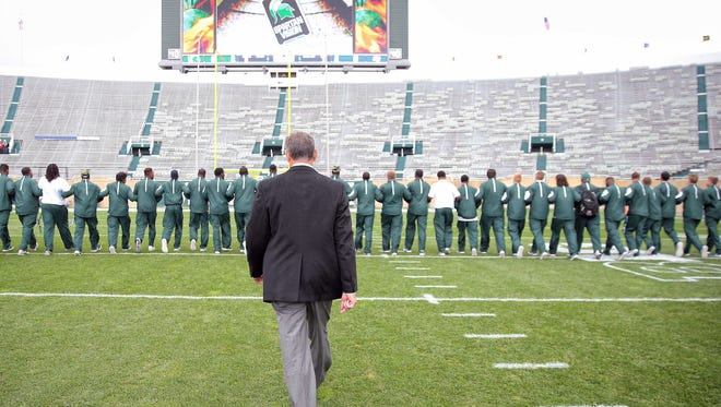 Michigan State Spartans head coach Mark Dantonio walks the field with his team prior to a game against Air Force at Spartan Stadium.