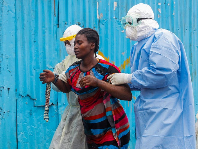 Nurses escort a suspected Ebola patient into the John F. Kennedy Ebola treatment center on Sept. 18 in Monrovia, Liberia.