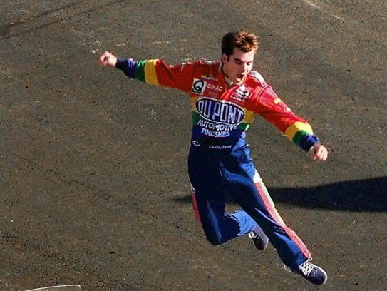 Jeff Gordon jumps from the roof of his car after winning