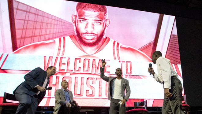Chris Paul waves to fans after being introduced as the newest member of the Rockets on July 14.