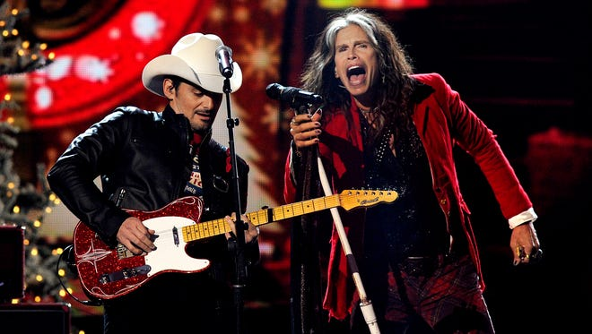 Aerosmith frontman Steven Tyler rocks out with Brad Paisley on â??Run Run Rudolphâ? during a taping for ABC special CMA Country Christmasat Bridgestone Arena.