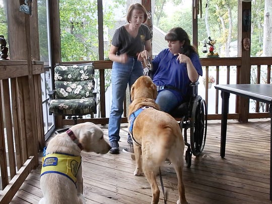 Louise and Kim work with the dogs on some tasks. Beachwood resident Kim Bratnik, 25,  has cerebral palsy and has a service dog Orson, that helps her do things around the house as well as at Kean College at Ocean County College where she's a student. Her mother Louise has joined in the effort to train service dogs for the companion dog program and has raised three service dogs. Photos taken at their Beachwood NJ  home on October 13, 2015.