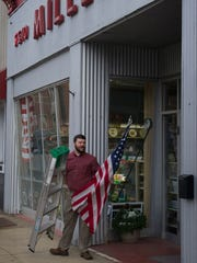 Like his grandfather, Jim Miller, had done since opening Miller's 5 & 10 in 1958, J.D. Campbell removes the American flag from the front of the Boonville, Ind., business Tuesday evening. J.D. and his wife, Jenny, now run the longtime family business.