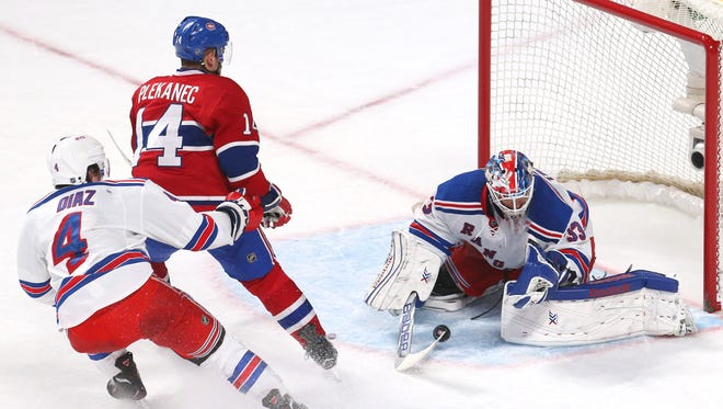 New York Rangers goalie Cam Talbot (33) makes a save against Montreal Canadiens center Tomas Plekanec (14) as defenseman Raphael Diaz (4) defends during the second period at Bell Centre.