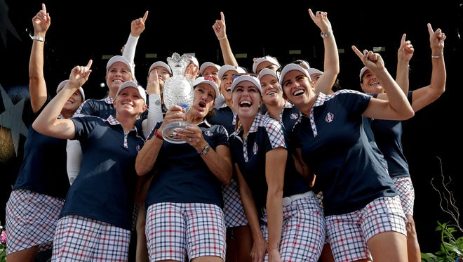 United States captain Juli Inkster, center, holds the Solheim Cup as she celebrates with her team after winning the Solheim Cup golf tournament, Sunday, Aug. 20, 2017, in West Des Moines, Iowa. (AP Photo/Charlie Riedel)