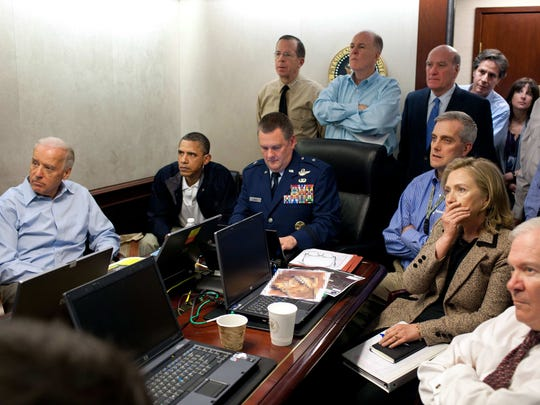 In this May 1, 2011, image released by the White House and digitally altered by the source to obscure the details of a document on the table, President Barack Obama, second from left, Vice President Joe Biden, left, Secretary of Defense Robert Gates, right, Secretary of State Hillary Rodham Clinton, second right, and members of the national security team watch an update on the mission against Osama bin Laden in the Situation Room of the White House in Washington.