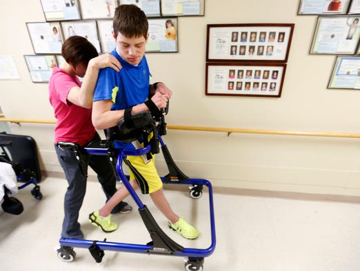 T.J. Denham, 17, takes steps with the help of physical therapist Jacque Thole at On With Life, a brain injury rehabilitation center in Ankeny.  T.J. became severely disabled after minor heart surgery one year ago. He can't talk, swallow, has little control of tho arms and legs and is restricted to a wheelchair. Doctors still are not sure what went wrong.