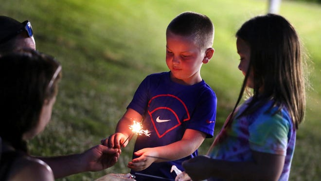 Hugh, 6, and Alice Dover, 9, light sparklers while waiting for fireworks to begin at Shelby City Park on Friday.