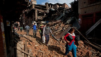 Nepalese residents carry belongings from their destroyed homes as they walk through debris of Saturday's earthquake, in Bhaktapur on the outskirts of Kathmandu, Nepal, on Monday.