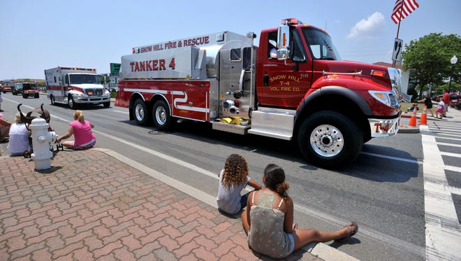 Members of the Snow Hill Volunteer Fire Company pass spectators during the Maryland State Firemen's Association's annual Firemen's Parade in Ocean City.