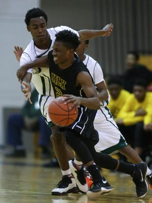 """Detroit King's Jesse Scarber drives against Detroit Douglass' James Smith during the fourth quarter Tuesday at Detroit Cass Tech. Scarber was King's defensive hero in the 58-44 win with three steals in the fourth. """"We had to step up our defense,"""" Scarber said."""