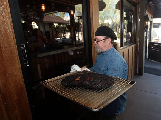 Chef Steven Helland with Smoketree BBQ in Palm Springs takes a brisket from the smoker into the restaurant on Tuesday.