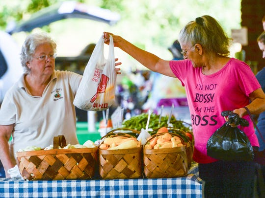 Twila Holliday, left, of Holliday's Veggie Patch, sells local farm-grown vegetables to Glenda Flannagan of Anderson, during morning activity at the Anderson County Farmer's Market in Anderson on Saturday.