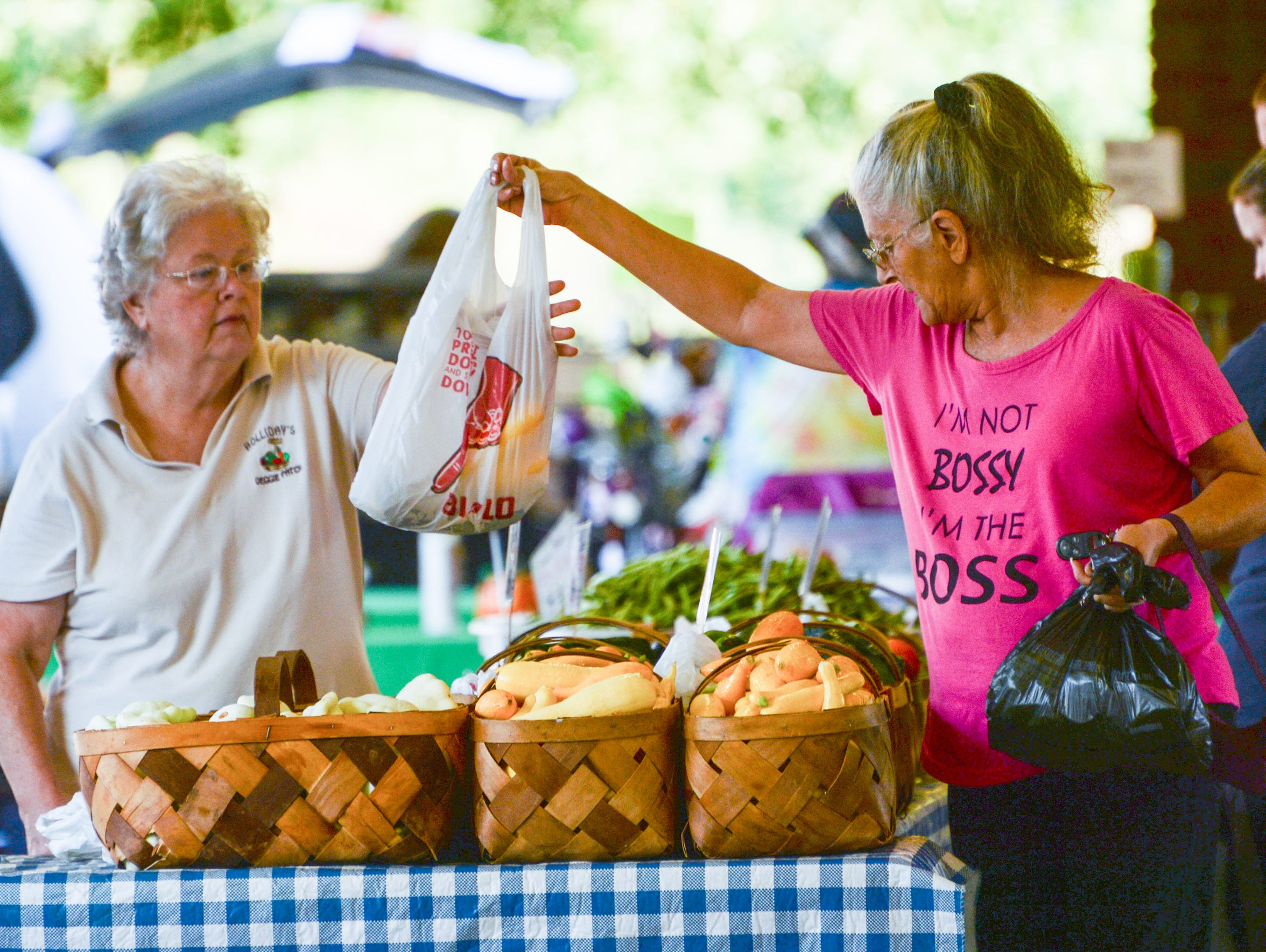 Twila Holliday, left, of Holliday's Veggie Patch, sells