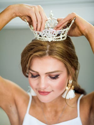 Alice Magoto places her Miss Ohio crown on her head at her home in Cincinnati Friday, August 26, 2016. Magoto is a graduate of Seton High School.