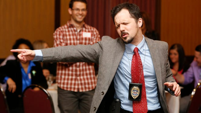 Nick Rowley, playing the role of detective Richard Less, gets excited about clues during a 2014 Dinner Detective event.