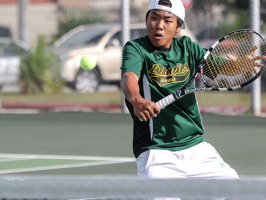 In this file photo, Chris Cajigan makes a backhand return to his opponent in an Independent Interscholastic Athletic Association of Guam Tennis League game.