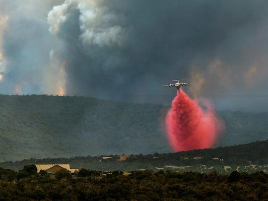 A fire fighting tanker drops retardant on the Dog Head